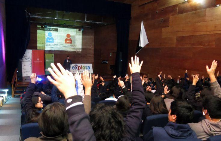 manos alzadas de estudiantes respondiendo consultas del expositor