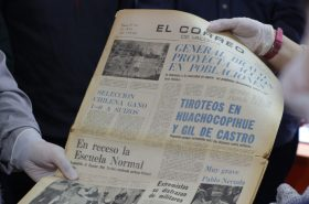 Un periódico antiguo tomado por dos manos con guantes. El periódico se llama El Correo de Valdivia.